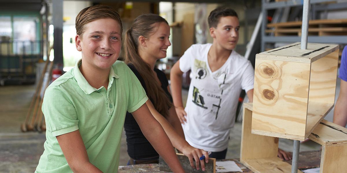 Kinderen op werkplaats met houten model