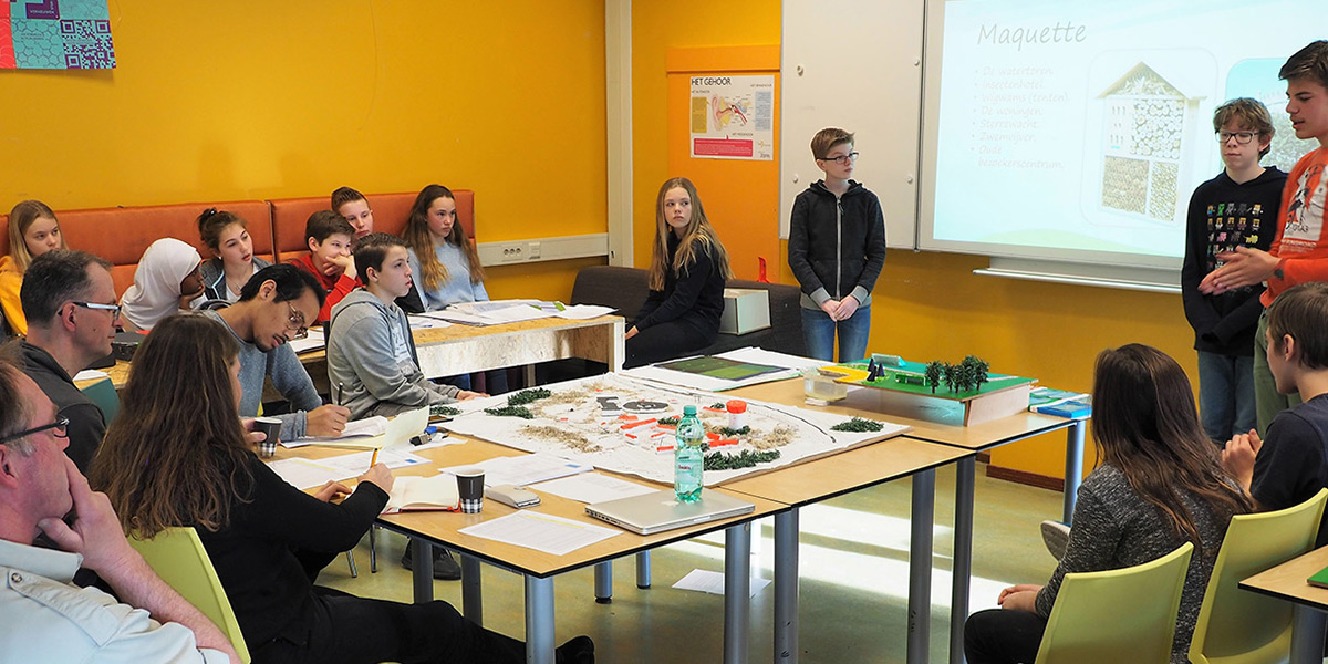 Klaslokaal met presentatie van groepje kinderen aan de rest van de klas
